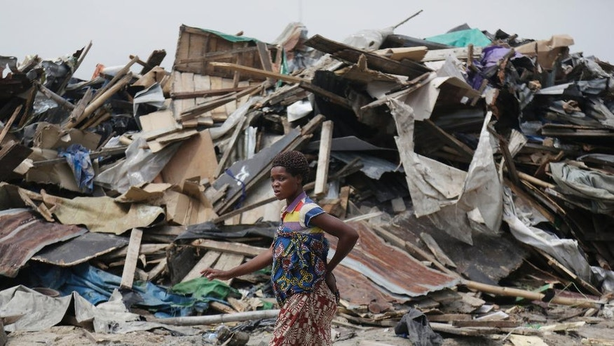A woman walks past demolished houses that were set ablaze by government officials in Lekki, Lagos, Nigeria. Saturday, Nov. 12, 2016, Amnesty International says as many as 30,000 people in Nigeria's commercial capital are homeless after their community was set ablaze and demolished this week. (AP Photo/Sunday Alamba)