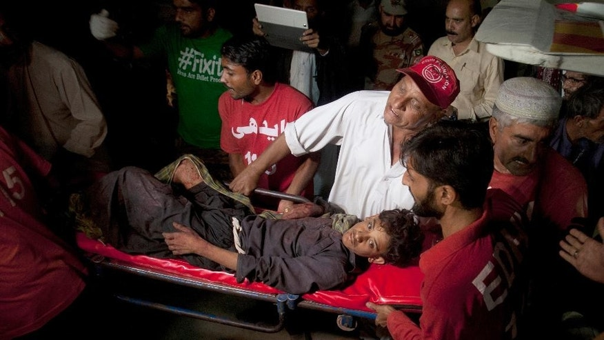 FILE - In this Saturday, Nov. 12, 2016, file photo, Pakistani rescue workers and volunteers carry an injured victim of a bomb blast at a Sufi shrine, upon his arrival at a local hospital in Hub town near Karachi, Pakistan. The Islamic State group claimed a bomb blast at a Sufi shrine that killed many people and wounded many others in the country's southwest. (AP Photo/Shakil Adil, File)