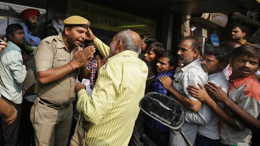 An Indian police officer pleads to an elderly man to stay in the queue as people crowd outside banks to deposit and exchange discontinued currency notes in New Delhi, India, Saturday, Nov. 12, 2016. Long lines have grown longer, scuffles have broken out and chaotic scenes are being seen across India as millions of people wait to change old currency notes that have become worthless after the government demonetized high-value bills. (AP Photo/Altaf Qadri)
