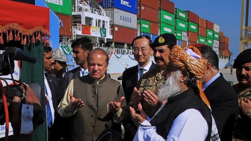Pakistan's Prime Minister Nawaz Sharif, center left, and Army Chief General Raheel Sharif, fourth right, pray after inaugurating a new international trade route during a ceremony at Gwadar port, about 435 miles, 700 km, west of Karachi. Pakistan, Sunday, Nov. 13, 2016. Pakistan's top civil and military leaders opened the new route by seeing off a Chinese ship that's exporting goods to the Middle East and Africa from the newly built Gwadar port. Chinese Ambassador to Pakistan Sun Weidong, center, attended. (AP Photo/Muhammad Yousuf)