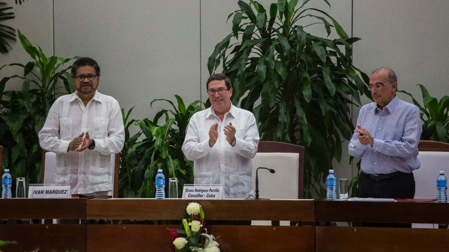 Ivan Marquez, chief negotiator of the Revolutionary Armed Forces of Colombia, or FARC, from left, Cuba's Foreign Minister Bruno Rodriguez, and Humberto de La Calle, head of Colombia's government peace negotiation team, applaud after the signing of the latest text of the peace accord between the two sides in Havana, Cuba, Saturday, Nov. 12, 2016. Colombia's government and the FARC signed a new, modified peace accord on Saturday following the surprise rejection of an earlier deal by voters in a referendum. (AP Photo/Desmond Boylan)