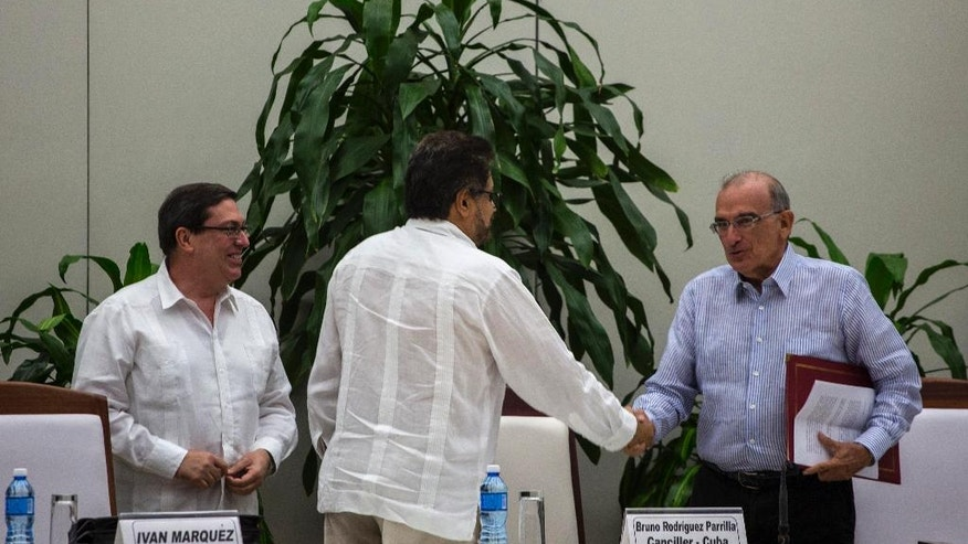 Humberto de La Calle, right, head of Colombia's government peace negotiation team, right, shakes hands with Ivan Marquez, chief negotiator of the Revolutionary Armed Forces of Colombia, or FARC, as Cuba's Foreign Minister Bruno Rodriguez, watches, after the signing of the latest peace accord between the two sides in Havana, Cuba, Saturday, Nov. 12, 2016. Colombia's government and its largest rebel group signed a new, modified peace accord on Saturday following the surprise rejection of an earlier deal by voters in a referendum. (AP Photo/Desmond Boylan)