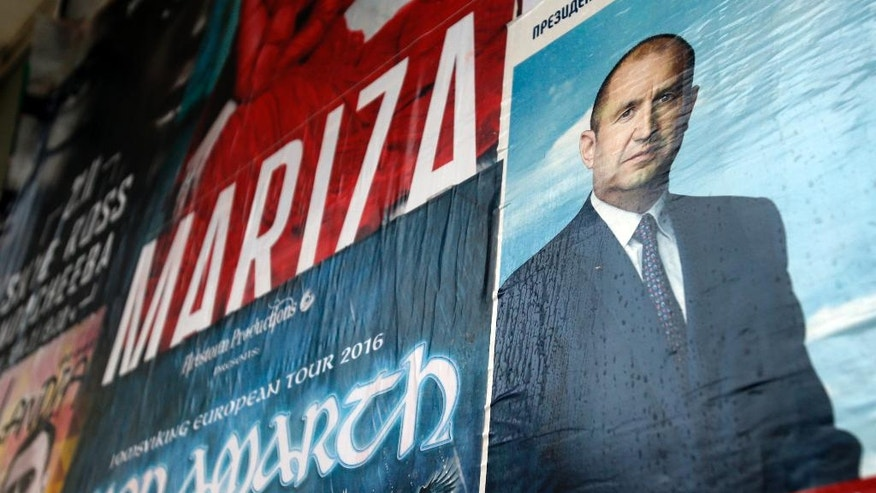 A poster on the wall shows Bulgarian Socialists Party candidate Rumen Radev, in downtown Sofia, Bulgaria, Saturday, Nov. 12, 2016. Bulgarians vote Sunday to choose their new president in a contested runoff that has become a referendum on the fate of the country's center-right government. (AP Photo/Darko Vojinovic)