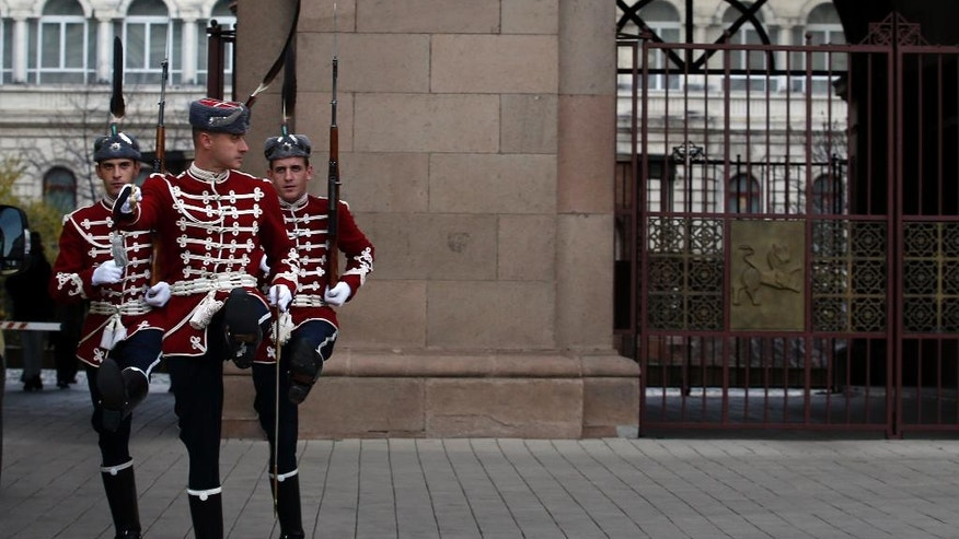 A Bulgarian guard of honor changes shifts in front of a presidency building in downtown Sofia, Bulgaria, Saturday, Nov. 12, 2016. Bulgarians vote Sunday to choose their new president in a contested runoff that has become a referendum on the fate of the country's center-right government. (AP Photo/Darko Vojinovic)