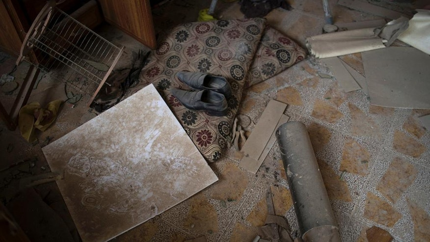 Shoes and artillery sit in the interior of a house formally used by Islamic State militants in Bashiqa, east of Mosul, Iraq, Friday, Nov. 11, 2016. Iraqi troops inched ahead in their battle to retake the northern city of Mosul from the Islamic State group on Friday, as the U.N. revealed fresh evidence that the extremists have used chemical weapons. (AP Photo/Felipe Dana)