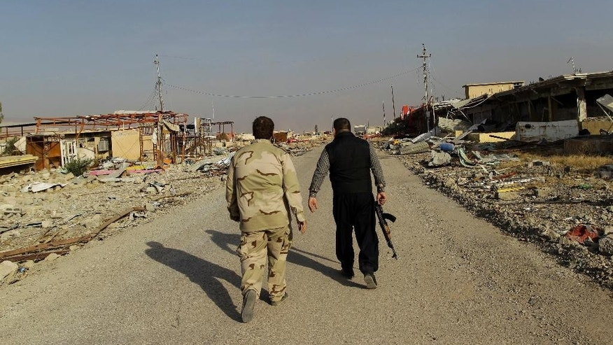 Ali Hussein, right, and his son walk to check on the family's used car business, which was looted by Islamic State fighters and destroyed in fighting to oust them in Bashiqa, east of Mosul, Iraq, Friday, Nov. 11, 2016. Iraqi troops inched ahead in their battle to retake the northern city of Mosul from the Islamic State group on Friday, as the U.N. revealed fresh evidence that the extremists have used chemical weapons. (AP Photo/Adam Schreck)