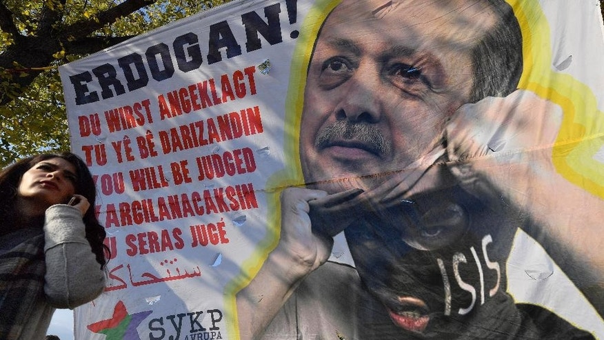 A banner shows an Islamic State group militant  unmasked as  Turkish president Recep Tayyip Erdogan, reading 'You will be judged' during a protest in Cologne, Germany, against the Turkish president  Erdogan and the political repression that followed July's failed military coup, Saturday, Nov. 12, 2016.  (AP Photo/Martin Meissner)