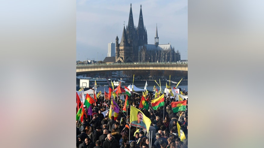 Pro-Kurdish  demonstrators protest  against Turkish president Recep Tayyip Erdogan and the political repression that followed July's failed military coup,  in Cologne, Germany Saturday, Nov. 12, 2016. People showing flags  with detained Kurdistan Workers Party, PKK , leader Abdullah Ocalan.   In background the Cologne cathedral.  (AP Photo/Martin Meissner)