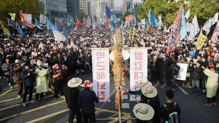 """Farmers burn an effigy symbolizing presidential house during a rally calling for South Korean President Park Geun-hye to step down in Seoul, South Korea, Saturday, Nov. 12, 2016. Tens, and possibly hundreds, of thousands of South Koreans were expected to rally in Seoul on Saturday demanding the ouster of Park in what would be one of the biggest protests in the country since its democratization about 30 years ago. The banner read """"Park Geun-hye should step down,"""" left, and """"Rise of rice price."""" (AP Photo/Ahn Young-joon)"""