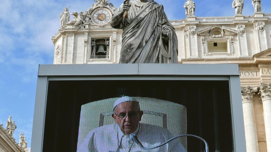 The statue of St. Peter towers over a screen which is broadcasting Pope Francis reading his message during a Jubilee audience in St. Peter's Square, at the Vatican, Saturday, Nov. 12, 2016. (AP Photo/Gregorio Borgia)