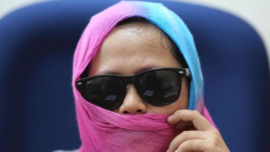 In this Sept. 7 photo, Harra Kazuo, live-in partner of alleged drug pusher Jaypee Bertes, covers her face to protect her identity during an interview at the Commission on Human Rights office in Quezon City, north of Manila, Philippines. Bertes was allegedly shot to death by police with his father-in-law following a drug raid which is part of the continuing anti-drugs campaign of Philippine President Rodrigo Duterte. The Commission on Human Rights has feared for her safety while it probes her case and has put her under an extraordinary witness protection program. (AP Photo/Aaron Favila)