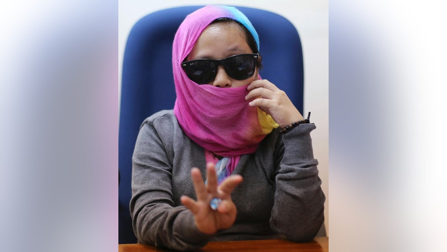 In this Sept. 7, 2016  photo, Harra Kazuo, live-in partner of alleged drug pusher Jaypee Bertes, gestures during an interview at the Commission on Human Rights office in Quezon City, north of Manila, Philippines. Kazuo's husband was shot to death by police with her father-in-law following a drug raid which is part of the continuing anti-drugs campaign of Philippine President Rodrigo Duterte. The Commission on Human Rights has feared for her safety while it probes her case and has put her under an extraordinary witness protection program. (AP Photo/Aaron Favila)