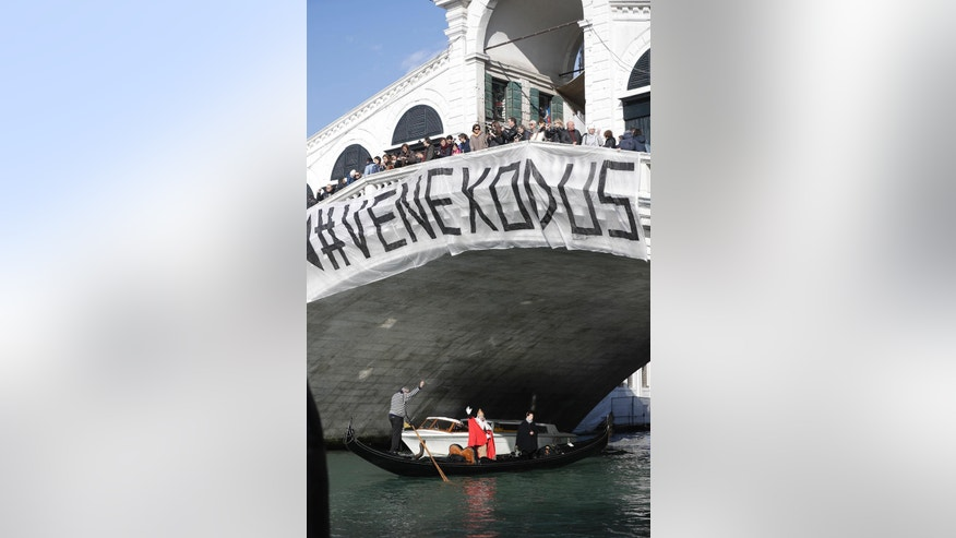 "A banner reading ""Venice Exodus"" is displayed on the Rialto Bridge as a protester on a gondola impersonates the ""Doge of Venice"" during a demonstration against the increasing number of tourists in Venice, Italy, Saturday, Nov.12. 2016. For decades, the number of Venetians have dwindled steadily and numerous factors are blamed _ high prices driven by a boom in tourism and the logistics of supplying a carless city and erosion by lapping waters among them. (AP Photo/Luca Bruno)"