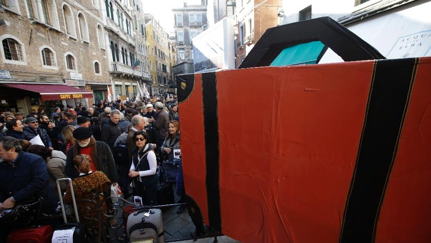 Demonstrators holding suitcases protest against the increasing number of tourists in Venice, Italy, Saturday, Nov.12. 2016. For decades, the number of Venetians have dwindled steadily and numerous factors are blamed _ high prices driven by a boom in tourism and the logistics of supplying a carless city and erosion by lapping waters among them. (AP Photo/Luca Bruno)