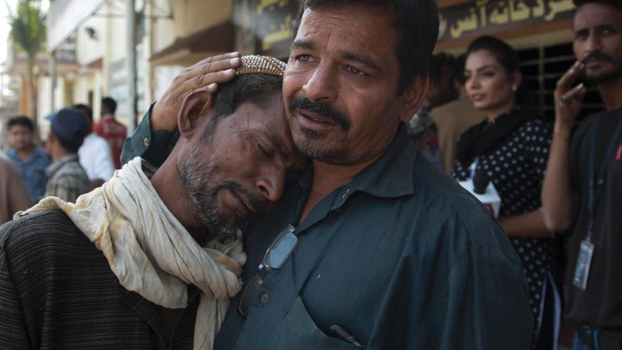 A Pakistani family member comforts Sabir, left, who lost his 16-year son Bilal in blast at a shrine which killed dozens of people, outside a morgue in Karachi, Pakistan, Sunday, Nov. 13, 2016. Bilal's father stepped outside, his brown salwar kameez soaked with sweat, tears rolling down his cheeks. Bilal had been his only son. He had brought the body to the mortuary to be washed in keeping with Islamic traditions. He would then be wrapped in a white shroud for burial. (AP Photo/B.K. Bangash)