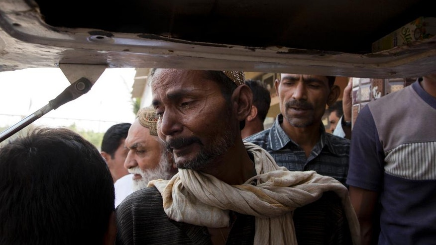 Pakistan's Sabir cries as he loads the dead body of his 16 year old son Bilal into an ambulance, after he was killed with many others during a blast at a shrine, at the Edhi Foundation mortuary in Karachi, Pakistan, Sunday, Nov. 13, 2016. Bilal had been his only son. He had brought the body to the mortuary to be washed in keeping with Islamic traditions. He would then be wrapped in a white shroud for burial. (AP Photo/B.K. Bangash)