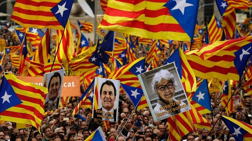 "Pro independence supporters wave ""estelada"" or pro independence flags, during a protest against a series of legal challenges made by Spain's government against pro-independence Catalan politicians in Barcelona, Spain, Sunday, Nov. 13, 2016. Several of Catalonia's lawmakers are facing court cases sought by the Spanish government for having staged a secession referendum in 2014 in disobedience of a court order and for other regional laws designed to prepare a path toward secession. Banners reads in Catalan: ""We are with you"" ""we are the dream"". (AP Photo/Manu Fernandez)"