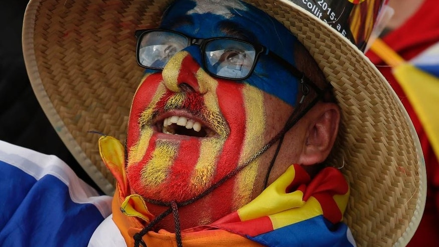 "A man with his face painted with the ""estelada"" or pro independence flag smiles during a protest against a series of legal challenges made by Spain's government against pro-independence Catalan politicians, in Barcelona, Spain, Sunday, Nov.13, 2016. Several of Catalonia's lawmakers are facing court cases sought by the Spanish government for having staged a secession referendum in 2014 in disobedience of a court order and for other regional laws designed to prepare a path toward secession. (AP Photo/Manu Fernandez)"