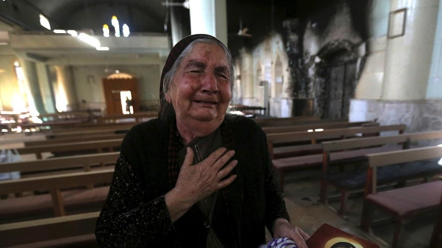A Christian Iraqi woman cries after she saw the St. Addai church which was damaged by Islamic State fighters during their occupation of Keramlis village, less than 18 miles, 29 kilometers, southeast of Mosul, Iraq, Sunday Nov. 13, 2016. There were gasps, and then tears, at the small church in northern Iraq as a group of Christians returned to their parish to find everything had been destroyed, including the statue of the Virgin Mary which IS militants decapitated before they left. The church bell tolled for the first time in more than two years, but few can summon up hope for the future. (AP Photo/Hussein Malla)