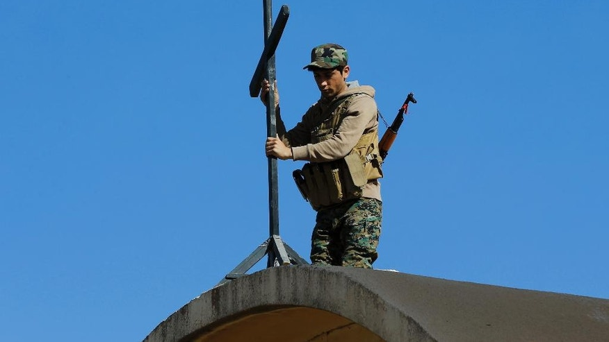 An Iraqi Christian soldier from Nineveh Plain Protection Unit sets a cross on top of the St. Addai Chaldean Catholic church, which was damaged by Islamic State fighters during their occupation of Keramlis village, less than 18 miles (29 kilometers) southeast of Mosul, Iraq, Sunday Nov. 13, 2016. There were gasps, and then tears, at the small church in northern Iraq as a group of Christians returned to their parish to find everything had been destroyed, including the statue of the Virgin Mary which IS militants decapitated before they left. The church bell tolled for the first time in more than two years, but few can summon up hope for the future. (AP Photo/Hussein Malla)