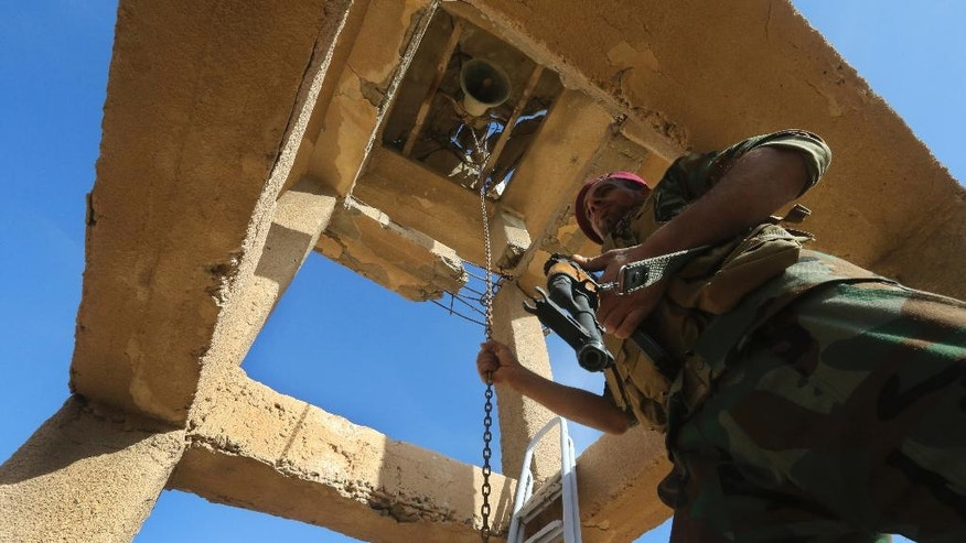 An Iraqi Christian soldier from Nineveh Plain Protection Unit rings the bell of the St. Addai Chaldean Catholic church, which was damaged by Islamic State fighters during their occupation of Keramlis village, less than 18 miles (29 kilometers) southeast of Mosul, Iraq, Sunday Nov. 13, 2016. There were gasps, and then tears, at the small church in northern Iraq as a group of Christians returned to their parish to find everything had been destroyed, including the statue of the Virgin Mary which IS militants decapitated before they left. The church bell tolled for the first time in more than two years, but few can summon up hope for the future. (AP Photo/Hussein Malla)