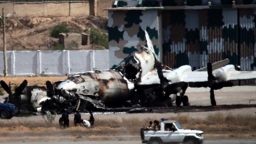 FILE - In this May 23, 2011 file photo, Pakistani troops drive past the wreckage of a gutted aircraft destroyed by militant attacks at a Pakistani Navy base in Karachi, Pakistan. The Islamic State group is increasing its presence in Pakistan, recruiting Uzbek militants, attracting disgruntled Taliban fighters and partnering with one of Pakistan's most violent sectarian groups, according to police officers, Taliban officials and analysts. (AP Photo/Shakil Adil, File)
