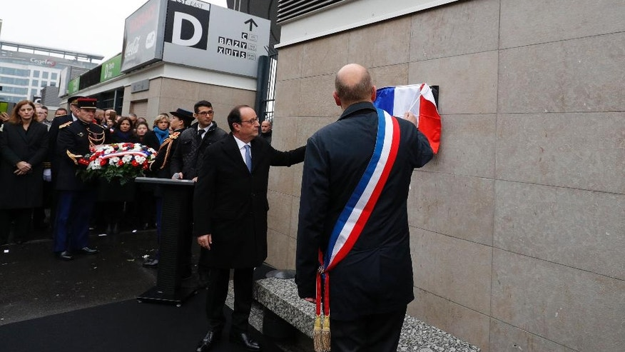 French President Francois Hollande and Saint-Denis mayor Didier Paillard, right, unveil a commemorative plaque outside the Stade de France stadium, in Saint-Denis, near Paris, France, Sunday, Nov. 13, 2016, during a ceremony held for the victims of last year's Paris attacks which targeted the Bataclan concert hall as well as a series of bars and killed 130 people. (Philippe Wojazer/Pool Photo via AP)