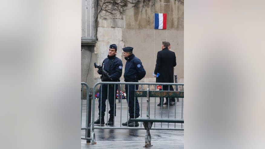 Police officers guards the attack sites at restaurant Le Petit Cambodge (Little Cambodia) and the Carillon Hotel in Paris, prior to the arrival of French President Francois Hollande to unveil a commemoration plate, Sunday, Nov. 13, 2016. A year ago the Islamic State group brought its extremist war to Paris, seeding terror with attacks on a rock concert, the national stadium and bustling sidewalk cafes. (AP Photo/Michel Euler)