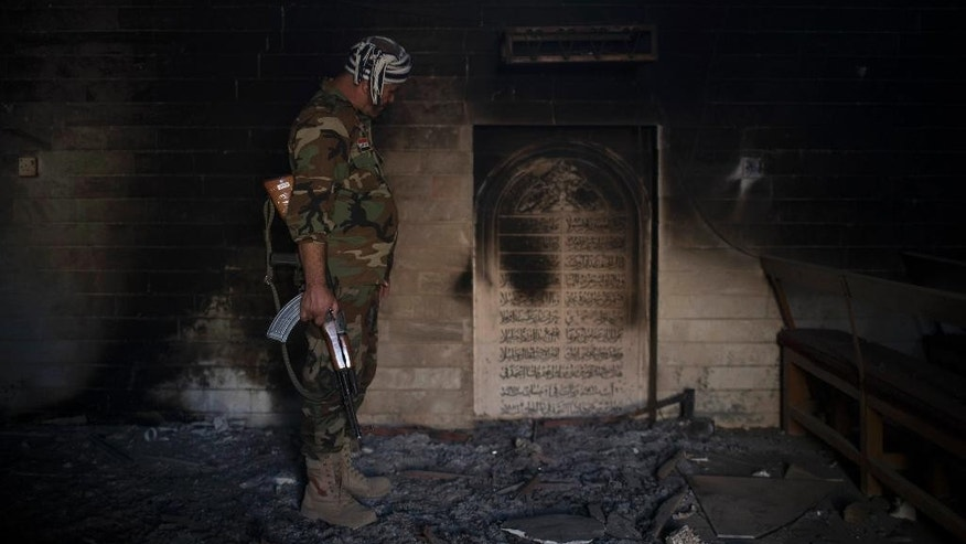 A Nineveh Plain Protection Units, or NPU, fighter inspects the interior of a church damaged by Islamic State fighters during their occupation of Qaraqosh, east of Mosul, Iraq, Saturday, Nov. 12, 2016. Qaraqosh, the biggest Christian town on the Nineveh plains in Iraq's north, fell to the Islamic State group in 2014 and was recently retaken by Iraqi government forces. (AP Photo/Felipe Dana)