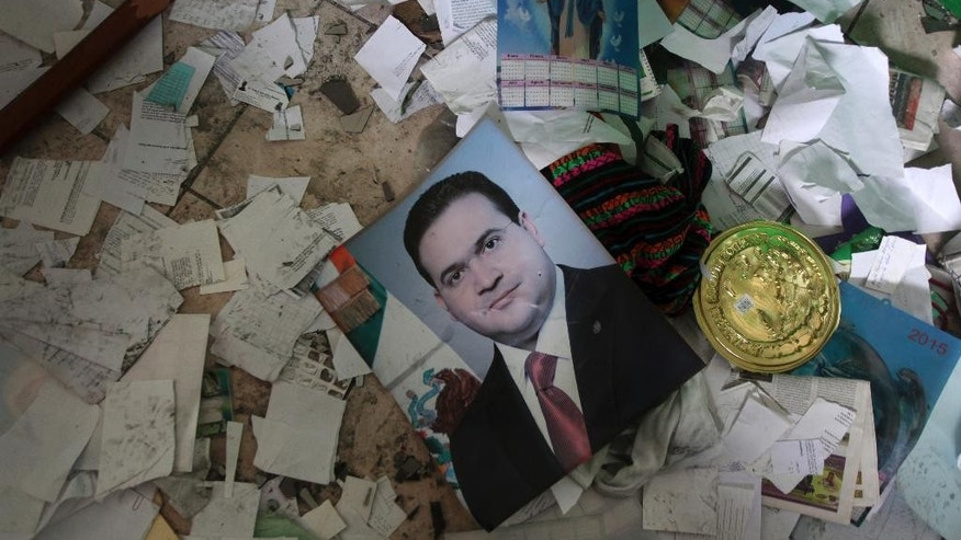 "A portrait of the former Governor of Veracruz lays in the middle of debris after the Municipal Palace in Catemaco, Veracruz, was set on fire, Sunday, Nov. 13, 2016. Two days of unrest were caused by the abduction three days ago of Rev. Jose Luis Sanchez Ruiz. Sanchez Ruiz has been found alive, but ""with notable signs of torture,"" the Roman Catholic Church said Sunday. (AP Photo/Felix Marquez)"