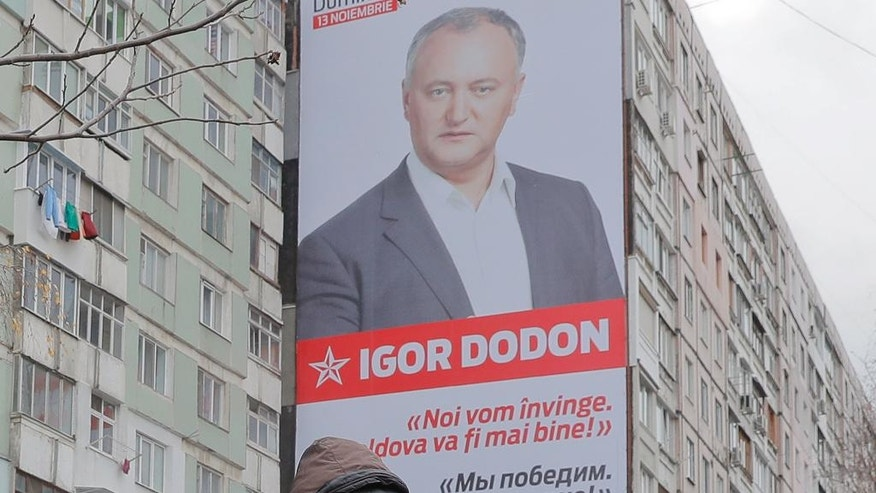 """A flower vendor stands back dropped by a large poster of socialist presidential candidate Igor Dodon, placed on an apartment block, which reads in Russian and Romanian """"We will win and it will be better in Moldova"""" in Chisinau, Moldova, Saturday, Nov. 12, 2016. Moldovans will directly elect their president on Sunday for the first time in 20 years the favorite is Socialist Igor Dodon, who wants the ex-Soviet republic to return to the Russian orbit, while rival Maia Sandu believes the agricultural nation of 3.5 million, bordering Ukraine and European Union member Romania, would secure a more prosperous future in Europe. (AP Photo/Vadim Ghirda)"""
