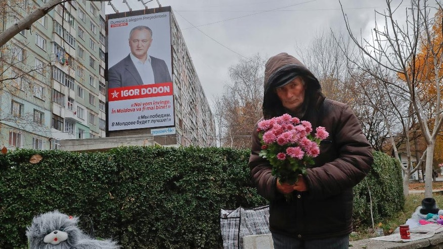 """A flower vendor stands back dropped by a large poster of socialist presidential candidate Igor Dodon, placed  displayed on an apartment block, which reads in Russian and Romanian """"We will win and it will be better in Moldova"""" in Chisinau, Moldova, Saturday, Nov. 12, 2016. Moldovans will directly elect their president on Sunday for the first time in 20 years the favorite is Socialist Igor Dodon, who wants the ex-Soviet republic to return to the Russian orbit, while rival Maia Sandu believes the agricultural nation of 3.5 million, bordering Ukraine and European Union member Romania, would secure a more prosperous future in Europe. (AP Photo/Vadim Ghirda)"""