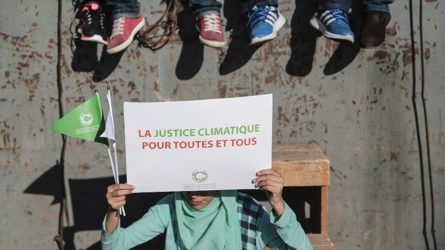 "A girl carries a sign saying ""Climate justice for all"" as she takes part in a protest against climate change coinciding with the Climate Conference, known as COP22, taking place in Marrakech, Morocco, Sunday, Nov. 13, 2016. (AP Photo/Mosa'ab Elshamy)"