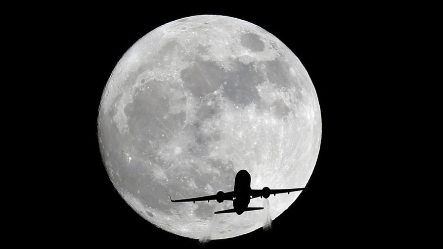 An American Airlines passenger plane passes in front of the moon, as seen from Whittier, Calif., Sunday, Nov. 13, 2016. Monday morning's supermoon will be the closet a full moon has been to the Earth since Jan. 26, 1948. (AP Photo/Nick Ut)