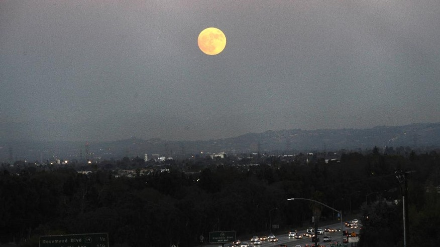 The moon rises above California 60 on Sunday, Nov. 13, 2016, in Rosemead, Calif. Monday morning's supermoon will be the closet a full moon has been to the Earth since Jan. 26, 1948. (AP Photo/Nick Ut)