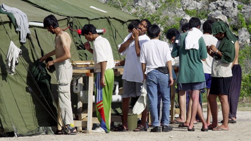 FILE - In this Sept. 21, 2001, file photo, men shave, brush their teeth and prepare for the day at a refugee camp on the Island of Nauru.