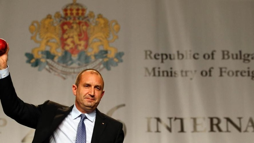 Bulgarian Socialists Party candidate Rumen Radev gestures with an apple during a press conference after presidential elections in Sofia, Bulgaria, Sunday, Nov. 13, 2016. Surveys by several polling organizations showed Gen. Rumen Radev, 53, a former non-partisan chief of Bulgarian Air Force, taking about 58 percent of the vote. (AP Photo/Darko Vojinovic)