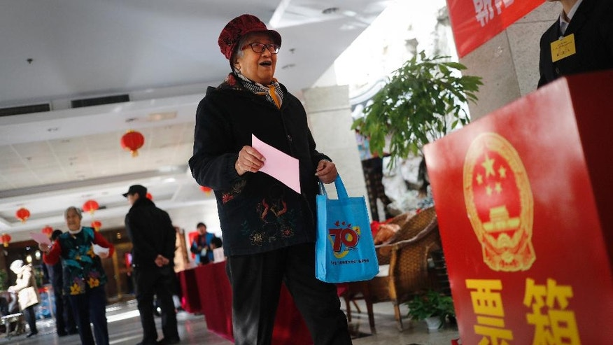 A woman prepares to cast her vote for representatives to the local district assembly known as the people's congress at a polling station set up in a residential building in Beijing, Tuesday, Nov. 15, 2016. Chinese authorities have responded to a small but determined group of independent candidates running in district elections with round-the-clock surveillance and confinement aimed at obstructing their efforts to build support. The controls reflect the ruling party's determination to maintain a rock-solid hold on politics at all levels, galvanized in recent years by President Xi Jinping's steady accumulation of political authority that has made him the most powerful Chinese leader since the 1980s. (AP Photo/Andy Wong)