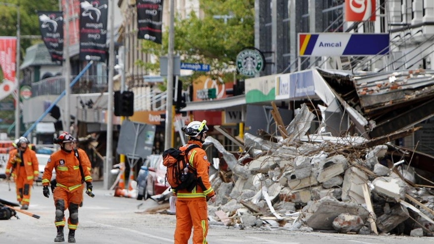 FILE - In this Feb. 26, 2011 file photo, representatives from the United Kingdom Fire and Rescue Service inspect the earthquake-damaged buildings in Colombo Street in Christchurch, New Zealand, following a magnitude 6.3 temblor. A powerful earthquake struck New Zealand on Monday, Nov. 14, 2016, reminding many of the quake that hit the nation in February 2011 and devastated the city of Christchurch, the country's second-biggest city. (AP Photo/Mark Baker, File)