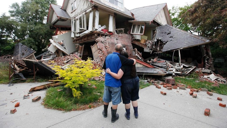 FILE - In this Feb. 23, 2011 file photo Murray, left, and Kelly James look at their destroyed house in central Christchurch, New Zealand, a day after a deadly earthquake. A powerful earthquake struck New Zealand on Monday, Nov. 14, 2016, reminding many of the quake that hit the nation in February 2011 and devastated the city of Christchurch, the country's second-biggest city. (AP Photo/Mark Baker, File)