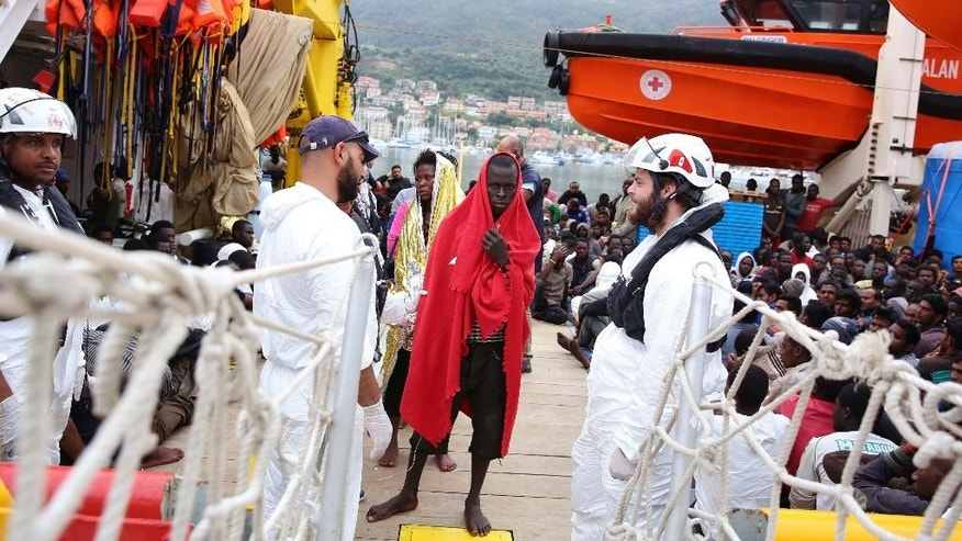 Migrants wrapped in blankets disembark from the vessel Responder, run by the Malta-based NGO Migrant Offshore Aid Station (MOAS) and the Italian Red Cross, in Vibo Valentia, southern Italy, on Monday, Nov. 7, 2016. About 400 disembarked after being rescued at sea in separate operations. (Francesco Malavolta/MOAS via AP)