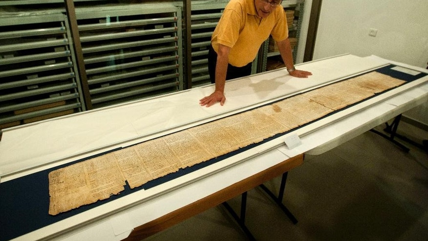 FILE - In this Monday, Sept. 26, 2011 file photo, Dr. Adolfo Roitman presents a part of the Isaiah Scroll, one of the Dead Sea Scrolls, inside the vault of the Shrine of the Book building at the Israel Museum in Jerusalem. An Israeli antiquities official says Israel is embarking on a major expedition to find more Dead Sea Scrolls and other artifacts. (AP Photo/Sebastian Scheiner, File)