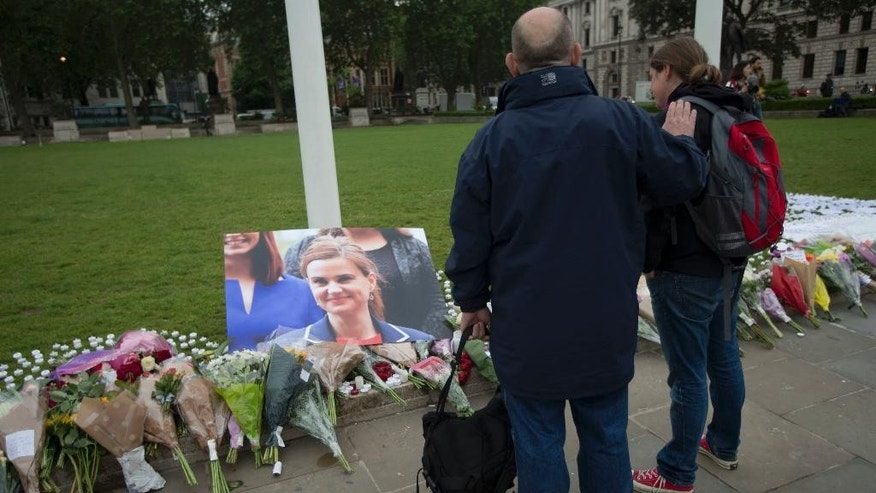 FILE - In this Friday, June 17, 2016 file photo, people look at tributes for Jo Cox, the 41-year-old British Member of Parliament shot to death yesterday in northern England, on Parliament Square outside the House of Parliament in London. Thomas Mair goes on trial, Monday Nov. 14, 2016, accused of murdering lawmaker Jo Cox, who was slain in the street a week before Britain's EU referendum in June. (AP Photo/Matt Dunham, File)