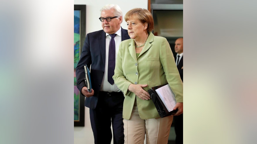 FILE - In this July 15, 2015 file photo German Chancellor Angela Merkel, right, and German Foreign Minister Frank-Walter Steinmeier arrive for the weekly cabinet meeting at the Chancellery in Berlin, Germany. (AP Photo/Michael Sohn, file)