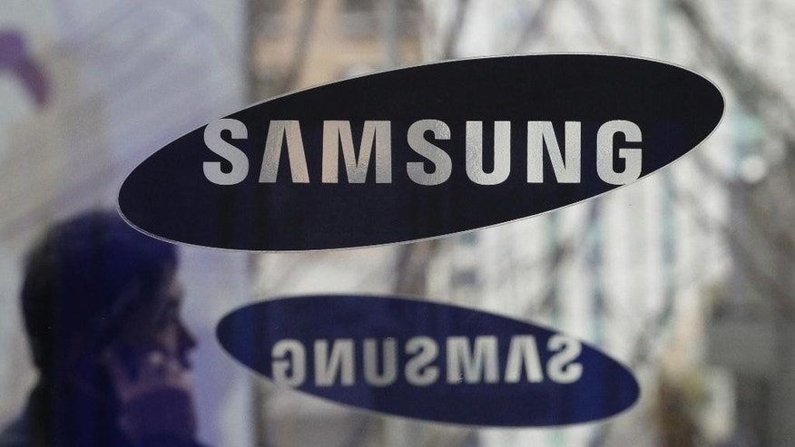 File - In this Dec. 12, 2013 file photo, a man with a mobile phone walks by the Samsung Electronics logos at its headquarters in Seoul, South Korea. Samsung Electronics said Monday, Nov. 14, 2016, it has agreed to acquire auto-systems maker Harman for $8 billion as the South Korean giant eyes the growing market for connected cars. (AP Photo/Ahn Young-joon, File)