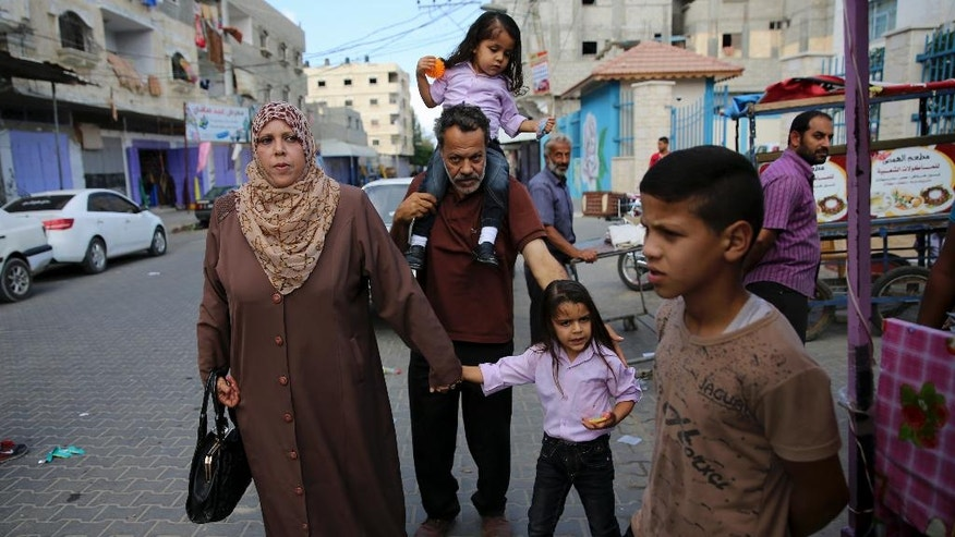 In this Oct. 31, 2016 photo, Syrian refugee Majed al-Attar carries his son Esam while his wife Manal holds the hand of their son Abdel Ghani, as they walk to the UNRWA clinic in the Rafah refugee camp, Gaza. Like millions of Syrians, the al-Attar family fled the civil war in their homeland in search of safety and security, but in a decision they now regret, they chose to go to Gaza. They are among 12 Syrian households that found refuge in Gaza after the civil war erupted in 2011 and are now trapped in the war-battered territory, but also unable to travel abroad. (AP Photo/Adel Hana)