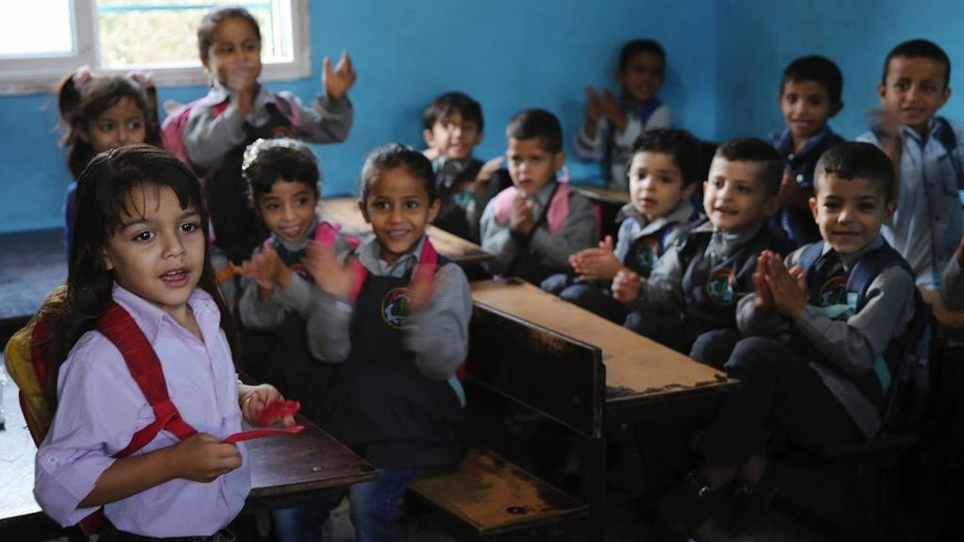 In this Oct. 31, 2016 photo, Abdel Ghani al-Attar, left, recites poetry to his classmates at a kindergarten in Rafah, Gaza. Like millions of Syrians, the al-Attar family fled the civil war in his homeland in search of safety and security, but in a decision they now regret, they chose to go to Gaza. Their family is among 12 Syrian households that found refuge in Gaza after the civil war erupted in 2011 and are now trapped in the war-battered territory, but also unable to travel abroad. (AP Photo/Adel Hana)
