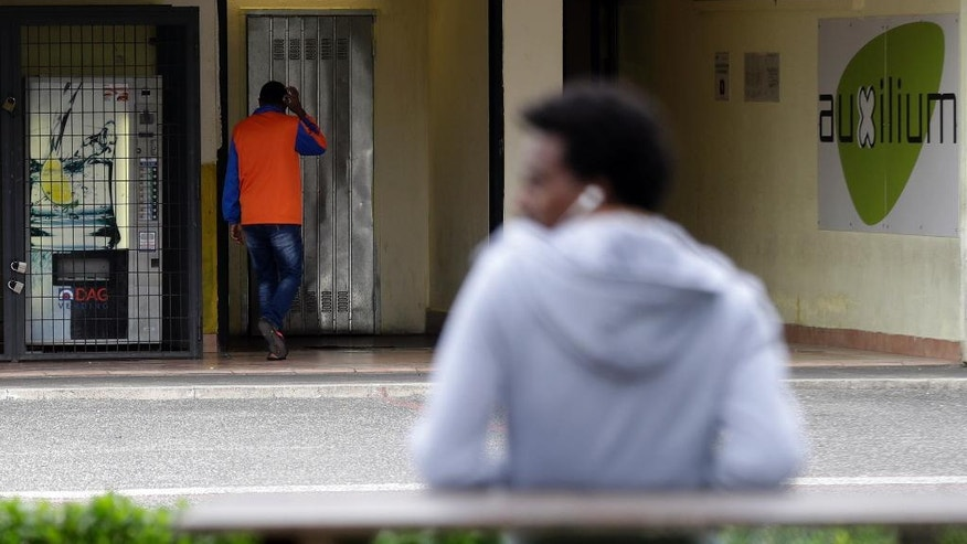 In this picture taken Monday, Nov. 14, 2016, migrants walk in the Castel Nuovo di Porto asylum seekers center, near Rome. Some 200 asylum-seekers, most of them Eritrean, are flown from Rome to Munich, Germany, as part of the European Union's relocation program.  (AP Photo/Gregorio Borgia)