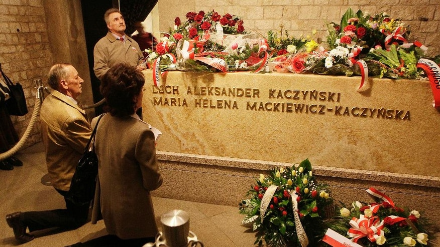 FILE - An April 18, 2011 file photo taken in the vaults of Wawel Cathedral in Krakow, Poland, showing the alabaster tomb of the late President Lech Kaczynski and his wife Maria Kaczynska who were killed, with 94 other prominent Poles, in a plane crash April 10, 2010 in Smolensk, Russia. The bodies of the presidential couple are being exhumed after dark on Monday, Nov. 14, 2016, for examination on orders from the prosecutors, who are investigating the crash.  (AP Photo/Czarek Sokolowski)