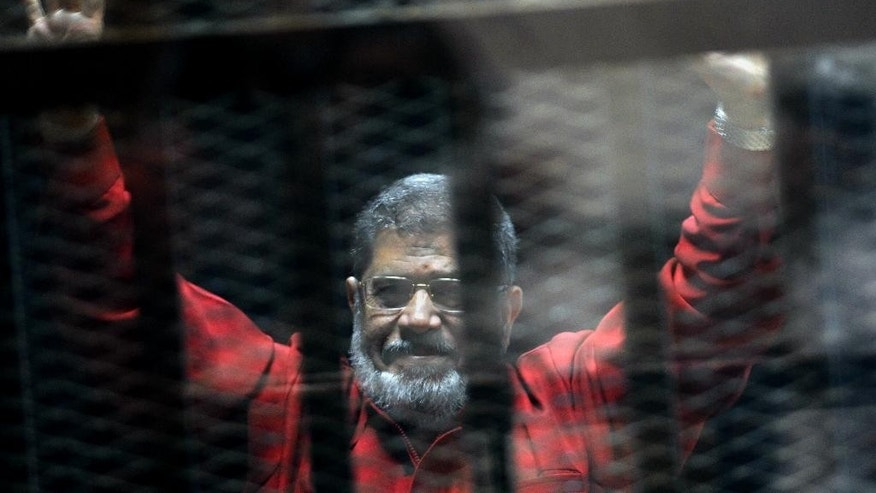 FILE - In this June 21, 2015 file photo, former Egyptian President Mohammed Morsi, wearing a red jumpsuit that designates he has been sentenced to death, raises his hands inside a defendants cage in a makeshift courtroom at the national police academy, in an eastern suburb of Cairo, Egypt. An Egyptian court on Tuesday, Nov. 15, 2016, struck down a death sentence passed by a lower tribunal against an ousted Islamist president for his part in a mass prison break during the country's 2011 uprising. The ruling means that Mohammed Morsi would be given a new trial, along with five other leaders of his now-banned Muslim Brotherhood group, whose death sentences in the same case were also quashed. (AP Photo/Ahmed Omar, File)